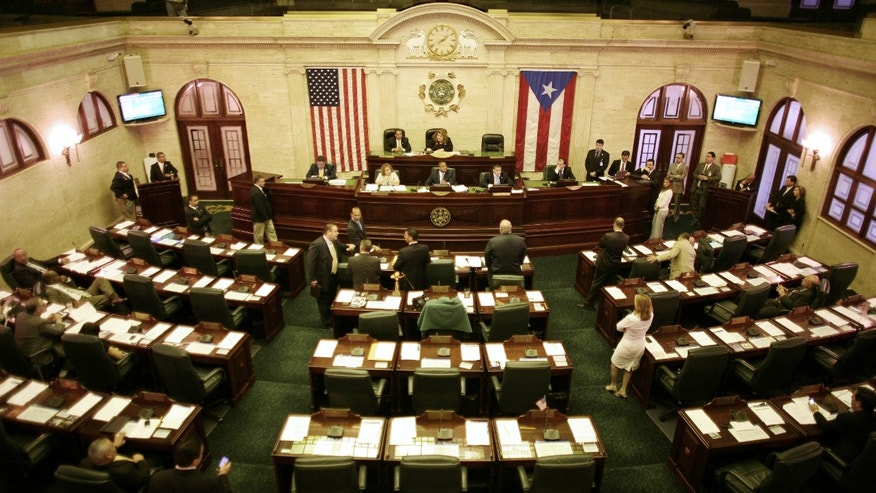 In this photo taken on Thursday, Jan. 11, 2012, members of the house attend a session at the capitol in San Juan, Puerto Rico. A voter referendum will ask the people of the U.S. island territory if they want to amend their Constitution and fire dozens of members of their Senate and House of Representatives as a cost-savings measure, reducing the size of the legislature by almost 30 percent. The answer is almost certain to be a resounding yes. (AP Photo/Ricardo Arduengo)