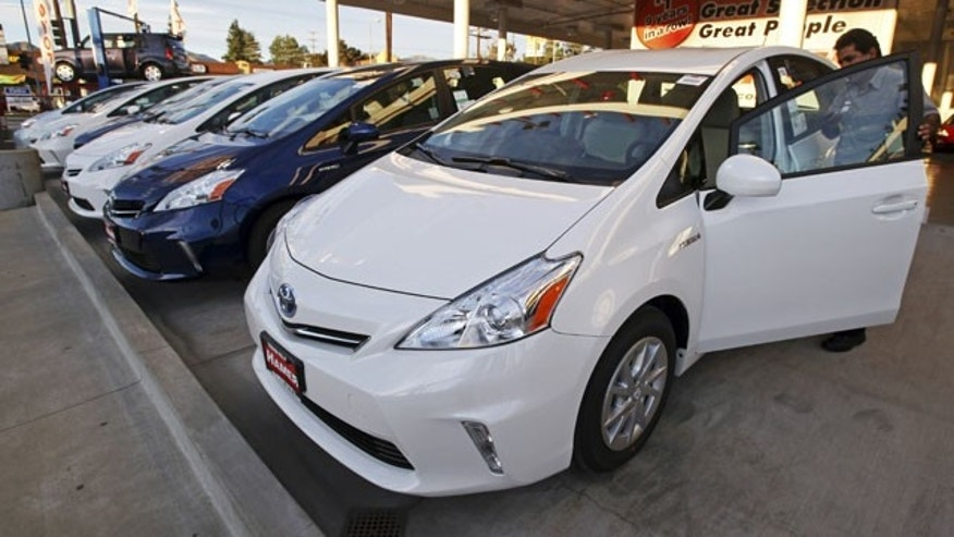 January 26, 2012: An employee parks a Toyota gas-electric hybrid automobile in a row of similar cars at a dealership in Los Angeles.