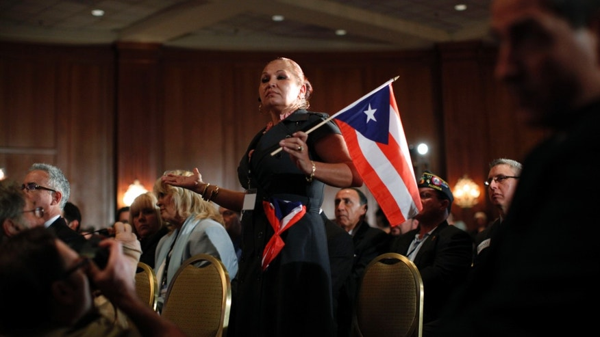 Elizabeth Cuevas-Neunder holds a Puerto Rican flag and asks Republican presidential candidate former House Speaker Newt Gingrich a question during the Hispanic Leadership Network conference at the Doral Golf Resort and Spa, Friday, Jan. 27, 2012, in Miami, Fla. Romney and Gingrich square off over immigration and other issues as they look to woo Hispanics a day after a feisty, final debate before Tuesday's Florida primary. (AP Photo/Matt Rourke)
