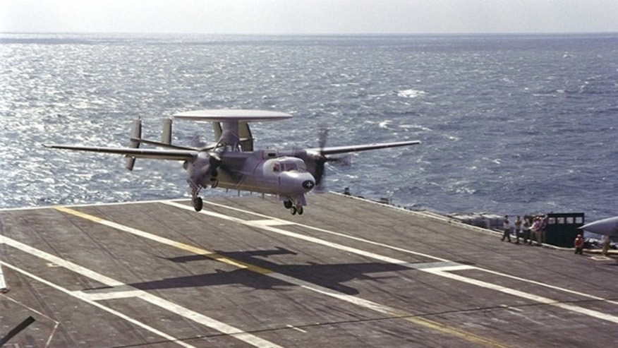 A Northrop Grumman E-2C Hawkeye 2000 surveillance and reconnaisance plane lands on a carrier.