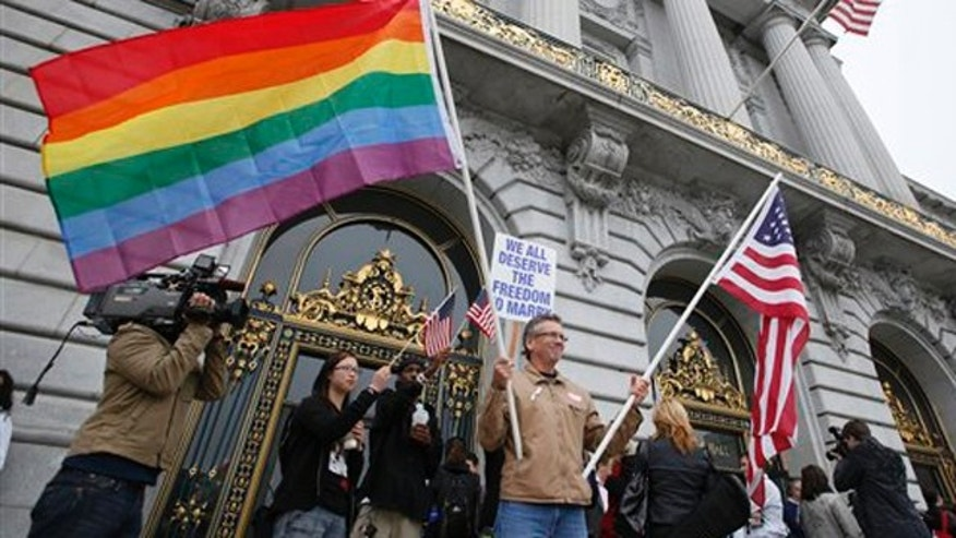 Aug. 12, 2010: Billy Bradford of Castro Valley, Calif., waves a pair of flags outside City Hall while same-sex couple line up to see if they can be married in San Francisco. A federal appeals court is ready to announce its ruling on whether California's same-sex marriage ban violates the constitutional rights of gays and lesbians.