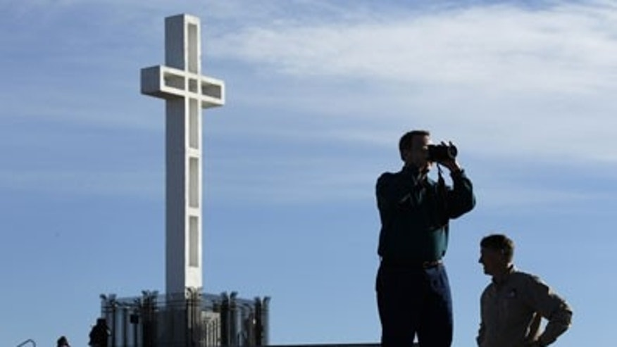 In this Jan. 4, 2011 file photo, Rev. John Fredericksen of Orlando, Fla., alongside Burdette Streeter, of San Diego, takes a picture in front of the war memorial cross on Mount Soledad in San Diego.