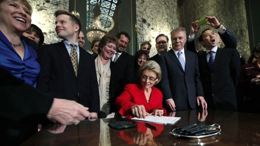 Feb. 13, 2012: Gov. Chris Gregoire, seated, is surrounded by legislators and supporters as she signs into law a measure that legalizes same-sex marriage in Olympia, Wash.