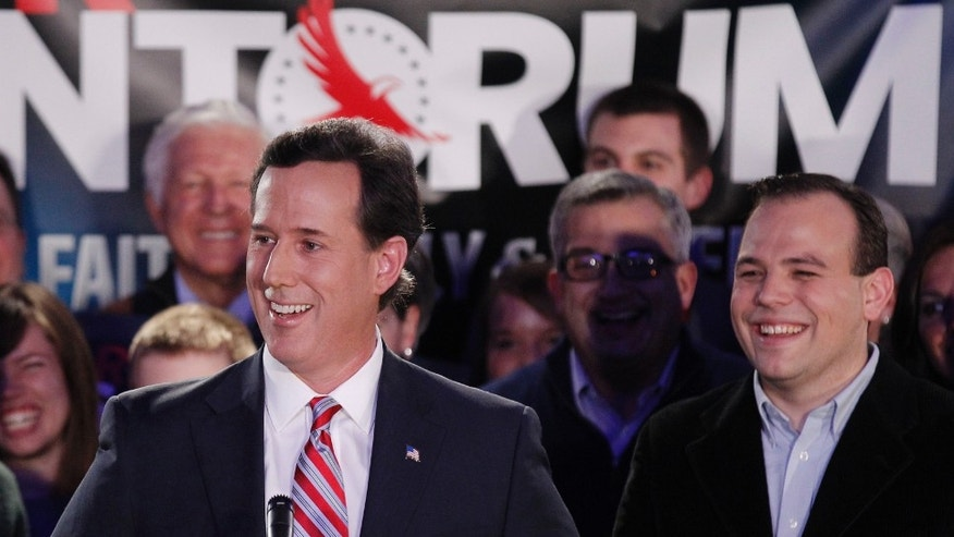 Republican presidential candidate, former Pennsylvania Sen. Rick Santorum, joined by wife Karen, left, addresses supporters at his Iowa caucus victory party Tuesday, Jan. 3, 2012, in Johnston, Iowa. (AP Photo/Charlie Riedel)