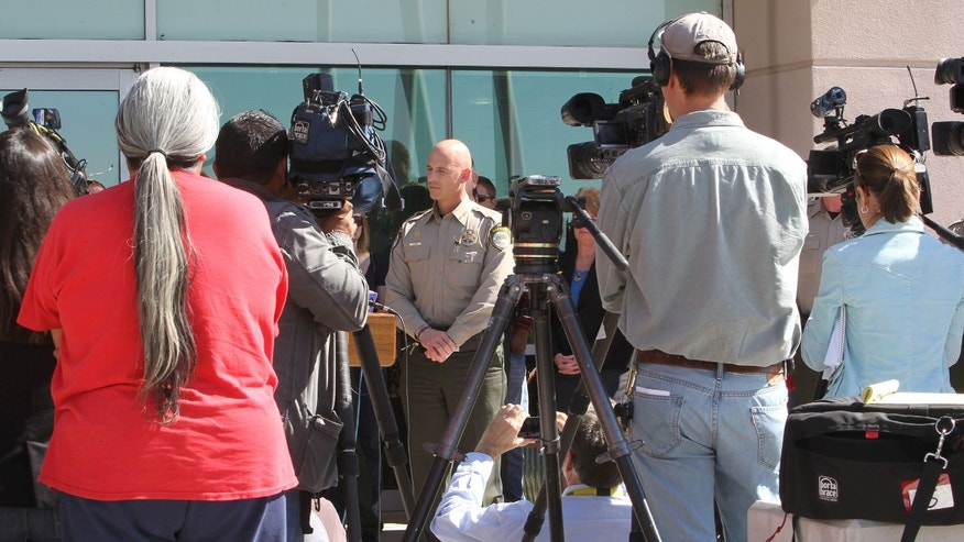 Pinal County Sheriff Paul Babeu, center, speaks at a news on Feb. 18 in Florence, Ariz. (AP Photo/The Arizona Republic, Deirdre Hamill)