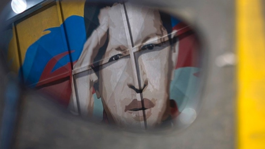 June 29: A motorcycle mirror reflects a painting depicting  Venezuela's President Hugo Chavez  in Caracas, Venezuela.AP Photo/Ariana Cubillos)