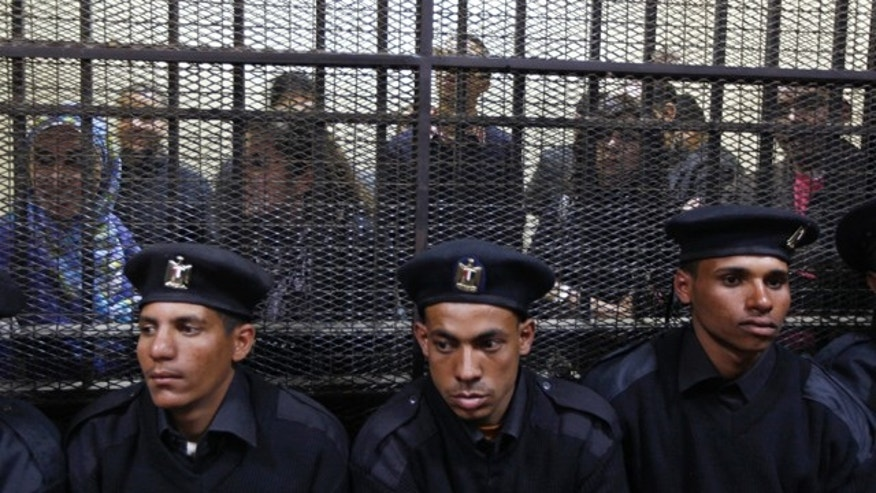 Feb. 26: Egyptian policemen sit in front of  Egyptian employees of several pro-democracy groups charged with using foreign funds to foment unrest during their trial in Cairo, Egypt.