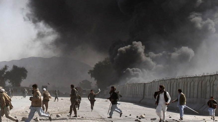 In this Feb. 22, 2012 file photo, protestors run as smoke rises from burning trucks during an anti-U.S. demonstration at a NATO military base in Jalalabad east of Kabul, Afghanistan.