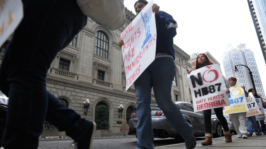 Pro immigration Demonstrators march outside the 11th U.S. Circuit Court of Appeals which is hearing arguments in the legal challenges against tough new laws targeting illegal immigration in Alabama and Georgia, Thursday, March 1, 2012, in Atlanta.  (AP Photo/John Amis)