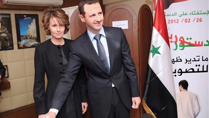Feb. 26, 2012: In this photo released by the Syrian official news agency SANA, Syrian President Bashar Assad casts his ballot next to his wife Asma at a polling station in Damascus, Syria.