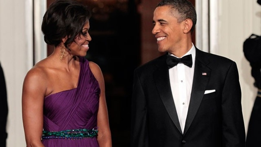 President Barack Obama and first lady Michelle Obama exchange smiles as they wait to greet South Korean President Lee Myung-bak and his wife Kim Yoon-ok at the North Portico of the White House in Washington, Thursday, Oct., 13, 2011, prior to a State Dinner.
