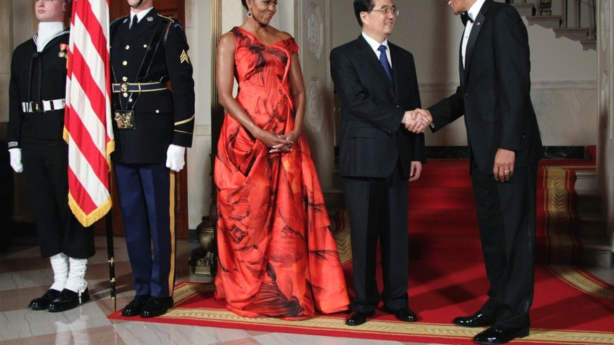 Jan. 19. 2011: President Barack Obama and first lady Michelle Obama greet China's President Hu Jintao at the Grand Staircase as they arrive for a state dinner at the White House in Washington. (AP)