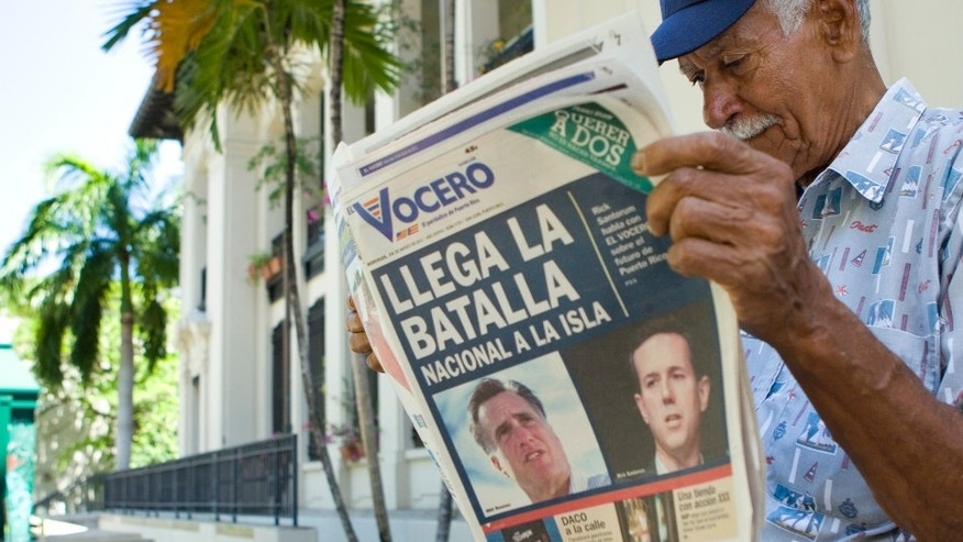 "SAN JUAN, PUERTO RICO - MARCH 14:  Carlos Diaz, 84, reads local newspaper El Vocero with a front page depicting both Mitt Romney and Rick Santorum and a headline reading, ""The National Battle Arrives on the Island.  (Photo by Christopher Gregory/Getty Images)"