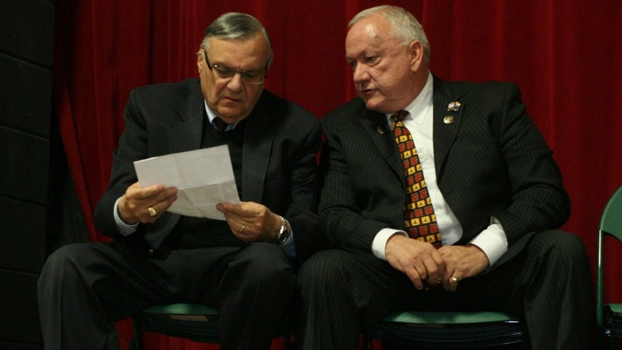 Maricopa County Sheriff Joe Arpaio,left, talks with Russell Pearce at an Arizona Red Mountain tea party meeting at East Valley High school in Mesa, Ariz. Monday, March 19, 2012. (AP Photo/Tim Hacker.East Valley Tribune)