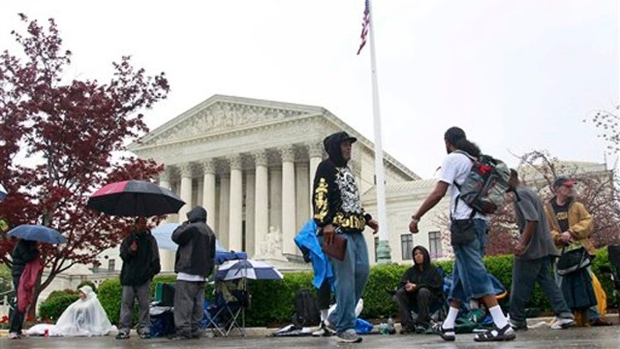 March 24, 2012: People walk in front of the Supreme Court as others form a line, in advance of arguments regarding the federal health care overhaul challenge.
