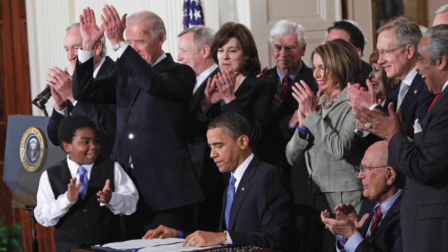 In this March 23, 2010 file photo, President Barack Obama is applauded after signing the health care bill in the East Room of the White House in Washington