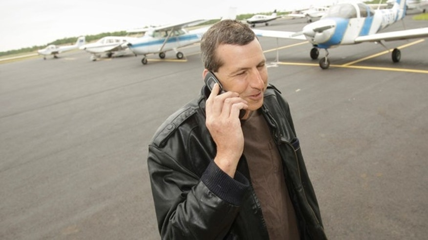 April 20, 2011: Commercial pilot Bill Phillips uses his cellphone on the tarmac at North Little Rock municipal Airport in North Little Rock, Ark.