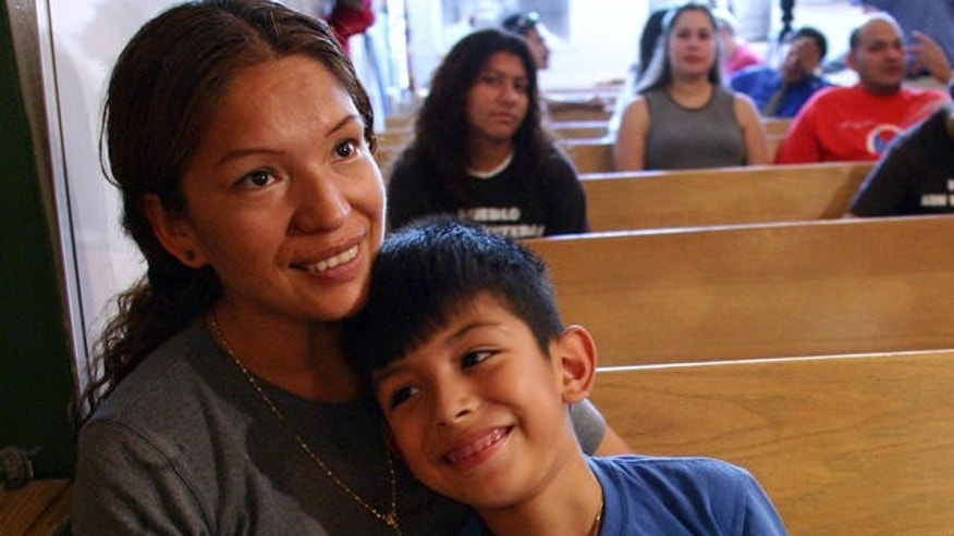 Elvira Arellano, left, sits with her 7-year-old son Saul Arellano, a U.S. citizen, on a pew inside Adalberto United Methodist Church in Chicago in 2006. Elvira lived in the church for about a year to avoid deportation to Mexico. She was arrested and deported after the left the church to speak at a rally.