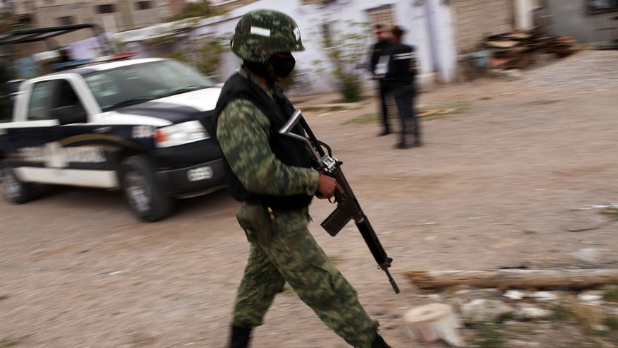 Military police stand guard at the scene of a murder on March 23, 2010 in Juárez, Mexico. (Photo by Spencer Platt/Getty Images)