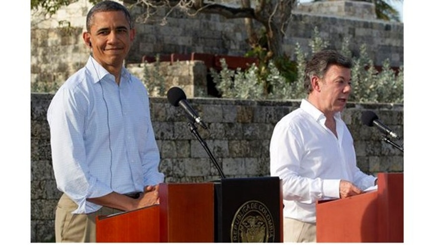 President Barack Obama, left, and Colombian President Juan Manuel Santos attend a joint news conference during the 6th Summit of the Americas in Cartagena, Colombia, Sunday, April 15, 2012. (AP Photo/Carolyn Kaster)