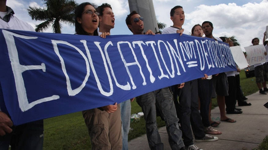 "POMPANO BEACH, FL - OCTOBER 25:  (L-R) Frida Ulloa, Felipe Mato and Raul Gil and others hold a sign reading, "" Education Not Deportation""' as they stand in front of the Broward Transitional Center on October 25, 2011 in Pompano Beach, Florida.  The group was protesting the possible deportation of Shamir Ali, a 25-year-old born in Bangladesh, who they say would be a candidate for the DREAM Act if it was made into a federal law. The DREAM Act bill would provide legal status to some undocumented young people.  (Photo by Joe Raedle/Getty Images)"