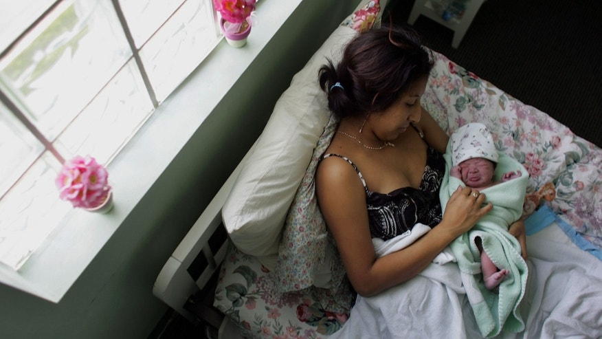 FLORIDA CITY, FL- OCTOBER 16:  Yailin Melissa Turcios, who was about 20 minutes prior, lies in the arms of her mother, Rosa Turcios, on a bed at the Birthing Center of South Florida October 16, 2006 in Florida City, Florida. This week the population of the United States will reach 300 million people. The excess of U.S. births over deaths accounted for about 1.7 million new Americans between 2004 and 2005, according to official figures. Another 1 million were added by immigration. The United States will remain the world's third most populous country after China and India.  (Photo by Joe Raedle/Getty Images)