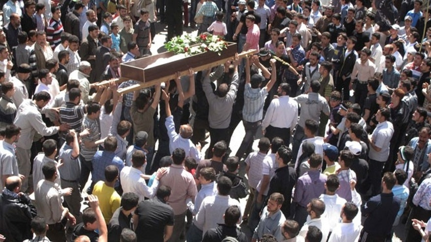 April 16, 2012: Syrians gather for a funeral for 6-year-old Yousef al-Najjar in Douma, a suburb of Damascus, Syria. The boy's family says he was shot in the chest when Syrian forces opened fire on the family car, seriously wounding his mother and infant brother.