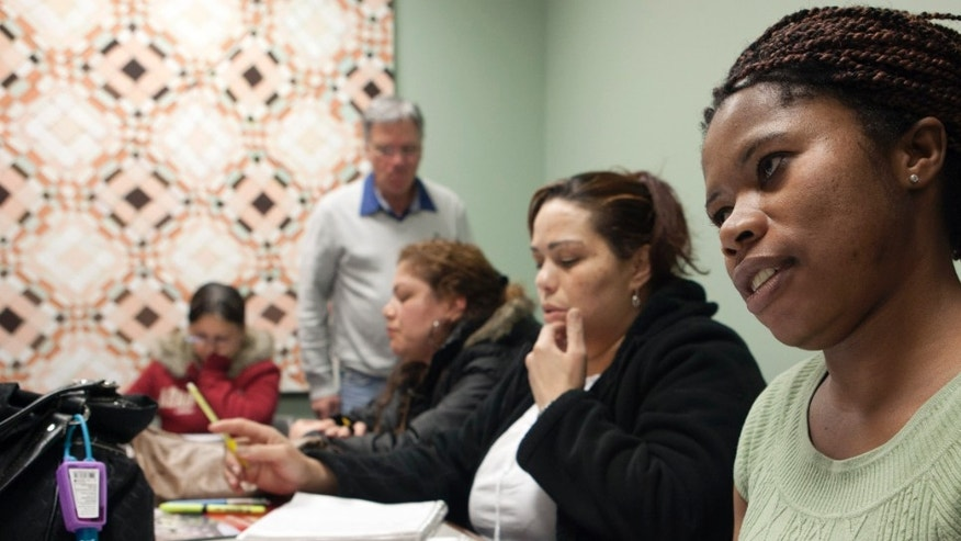In this photo taken March 16, 2012, immigrant Martha Johnson from Liberia, right, attends and American history and civic class in Chelsea, Mass., in preparation for a naturalization test. Hundreds of volunteers are helping qualified immigrants become U.S. citizens in time to register to vote in the November presidential elections.  (AP Photo/Rodrique Ngowi)