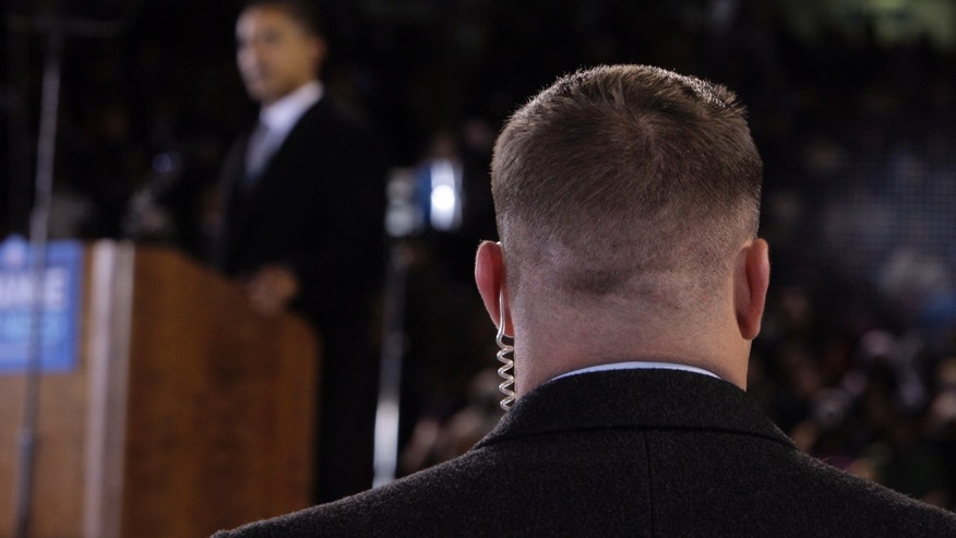 In this Oct. 28, 2008 file photo, a Secret Service agent stands near then presidential candidate Barack Obama, background, at a rally in Norfolk, Va. (AP Photo/Jae C. Hong, File)