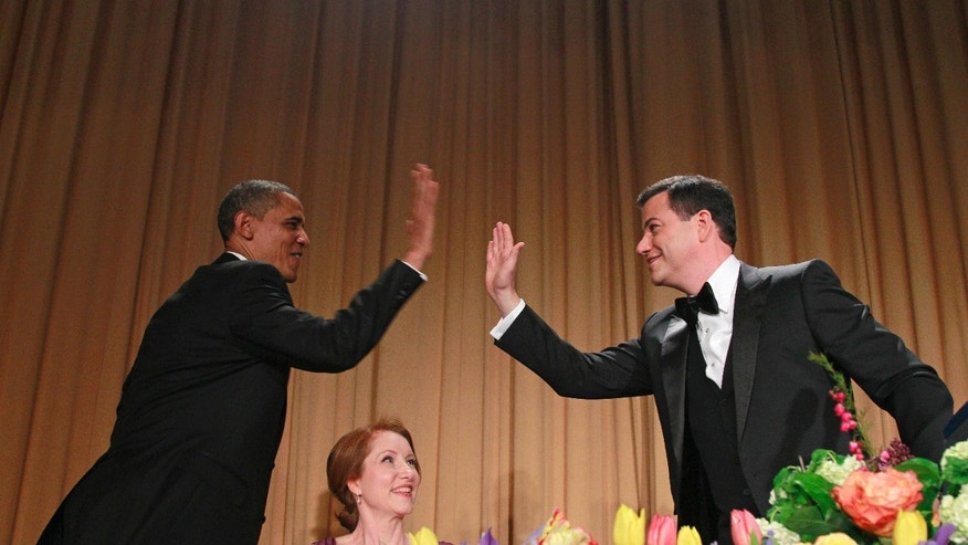 April 28, 2012: President Barack Obama high-fives late-night comic Jimmy Kimmel as Caren Bohan, a Reuters journalist and president of the White House Correspondents' Association looks on during the White House Correspondents' Association Dinner.