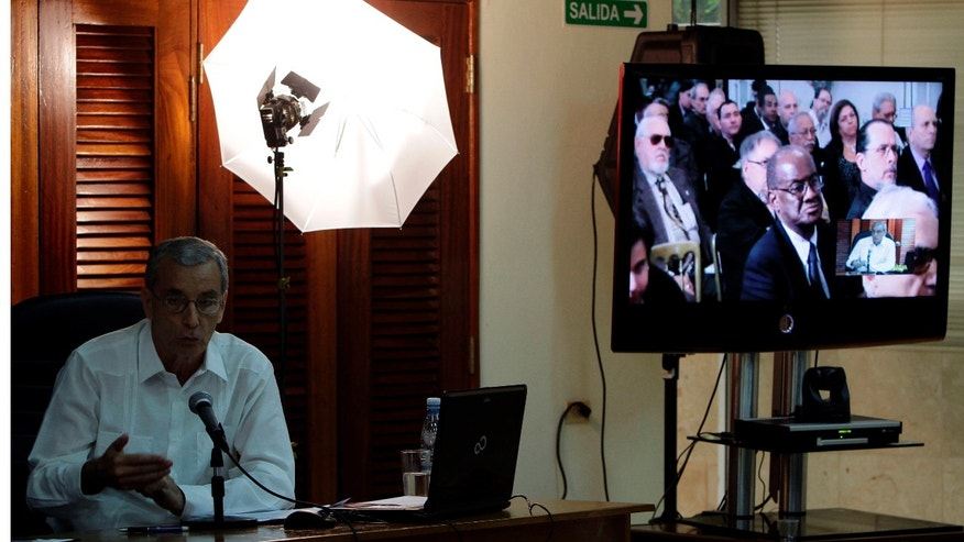 April 28: Economist Alberto Betancourt, left answers questions on Cuba's new economic reforms, posed by Cuban exiles in Washington D.C, shown on the screen at right, via a video conference at the Foreign Ministry in Havana, Cuba.  (AP Photo/Franklin Reyes)