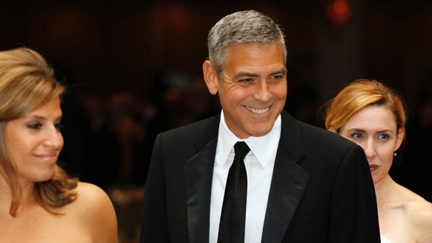 April 28, 2012: George Clooney, center, attends the White House Correspondents Association Dinner in Washington.