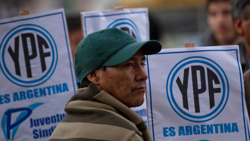 "A man stands in front of signs that read in Spanish ""YPF is Argentine"" outside the Congress as lawmakers debate the YPF bill in Buenos Aires, Argentina, Thursday, May 3, 2012. The lower house of Argentina's congress seemed certain to give the force of law to what Argentine President Cristina Fernandez surprisingly decreed two weeks earlier: the expropriation of Repsol's $10.5 billion stake in the country's YPF oil company, without a single centavo paid in advance. (AP Photo/Natacha Pisarenko)"
