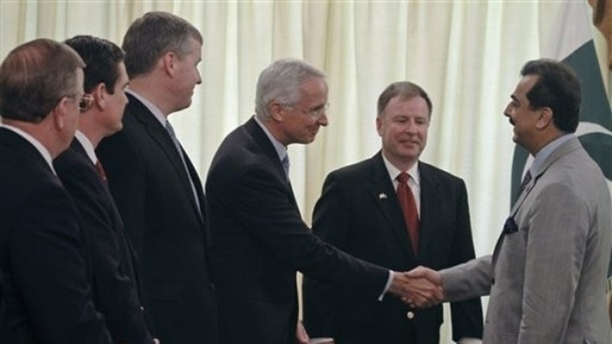 June 7, 2011: Pakistan's Prime Minister Yousuf Raza Gilani, right, shakes hand with U.S. Ambassador to Pakistan Cameron Munter as U.S. congressman Doug Lamborn, center looks on prior to their meeting in Islamabad, Pakistan.