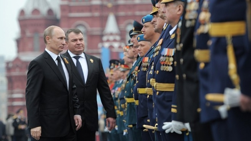 May 9, 2012: Russian President Vladimir Putin, left, and Defense Minister Anatoly Serdyukov, second left, speaks with officers and WWII veterans on the Red Square, after the Victory Day Parade, which commemorates the 1945 defeat of Nazi Germany in Moscow, Russia.