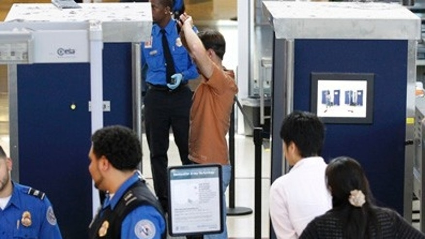 File: May 2011: A man is screened with a backscatter x-ray machine at a TSA security checkpoint at  Los Angeles International Airport.