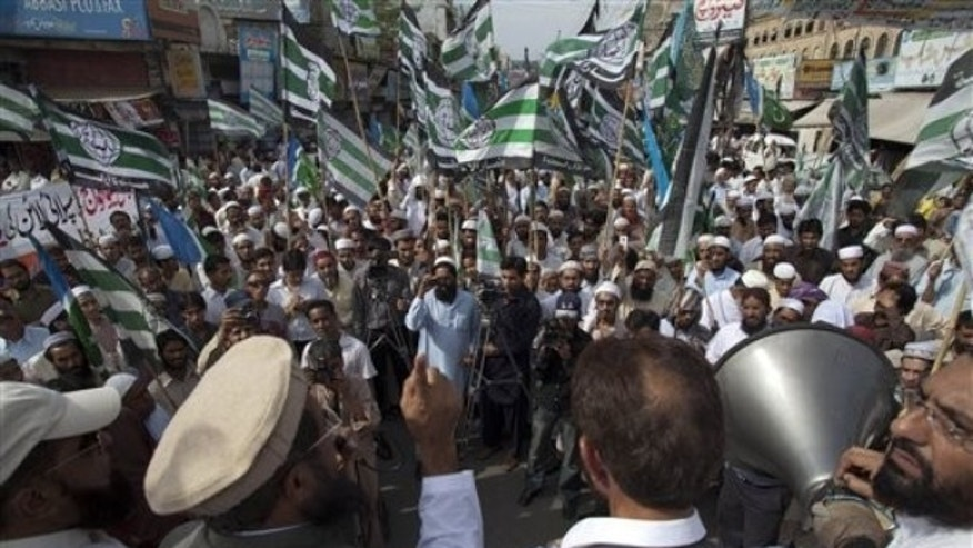 April 20, 2012: Pakistani religious leader Fazal-ur-Rehman Khalil, hand raised, addresses a protest rally to condemn reopening of the NATO supply line to neighboring Afghanistan, in Rawalpindi, Pakistan.