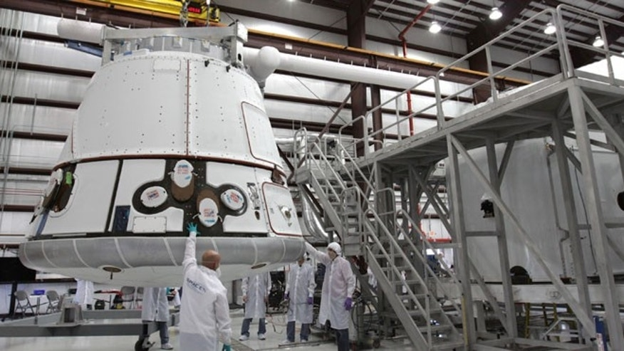 Nov. 16, 2011: The SpaceX Dragon capsule is lifted to be placed atop its cargo ring inside a processing hangar at Cape Canaveral Air Force Station in Florida.