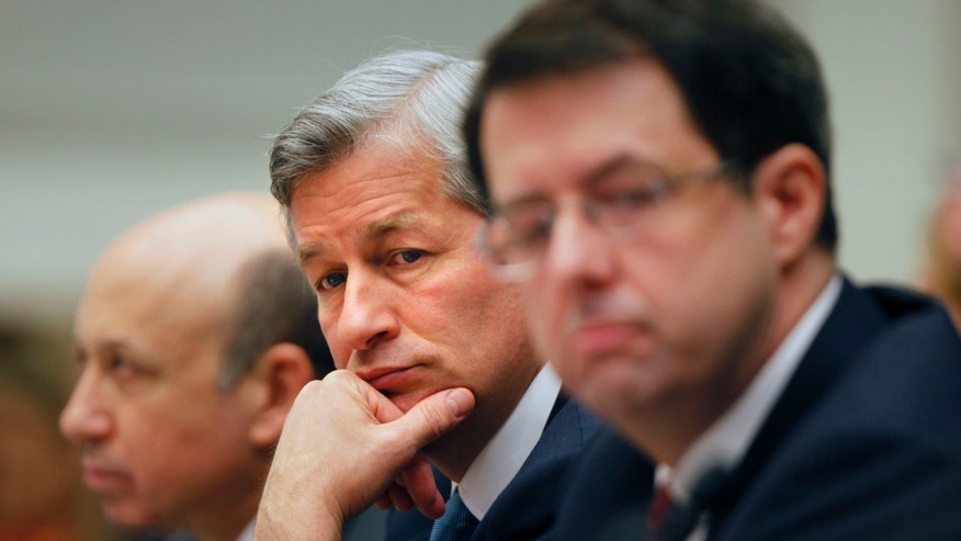 In this Feb. 11, 2009 file photo, JPMorgan Chase & Co. Chief Executive Officer Jamie Dimon, center, flanked by Goldman Sachs & Co. Chief Executive Officer and Chairman Lloyd C. Blankfein, left, and Bank of New York Mellon Chairman Chief Executive Officer Robert Kelly, are seen on Capitol Hill in Washington during a House Financial Services Committee hearing.