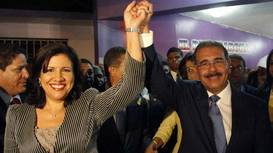 Danilo Medina, right, and Margarita Cedeno, presidential and vice presidential candidates of the ruling Dominican Liberation Party, celebrate at the party headquarters in Santo Domingo, Dominican Republic,  in the early hours of Monday, May 21, 2012. Medina and Cedeno, the current first lady, won the election in the first round with the 51.26% of the vote. (AP Photo/Manuel Diaz)