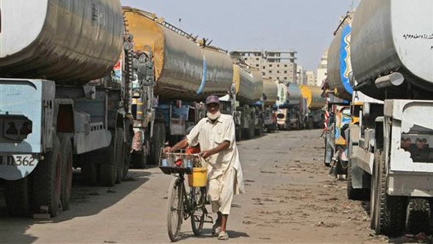 May 24, 2012: A Pakistani man selling cold drinks pushes his bicycle between oil tankers, which were used to transport NATO fuel supplies to Afghanistan, in a compound in Karachi, Pakistan.