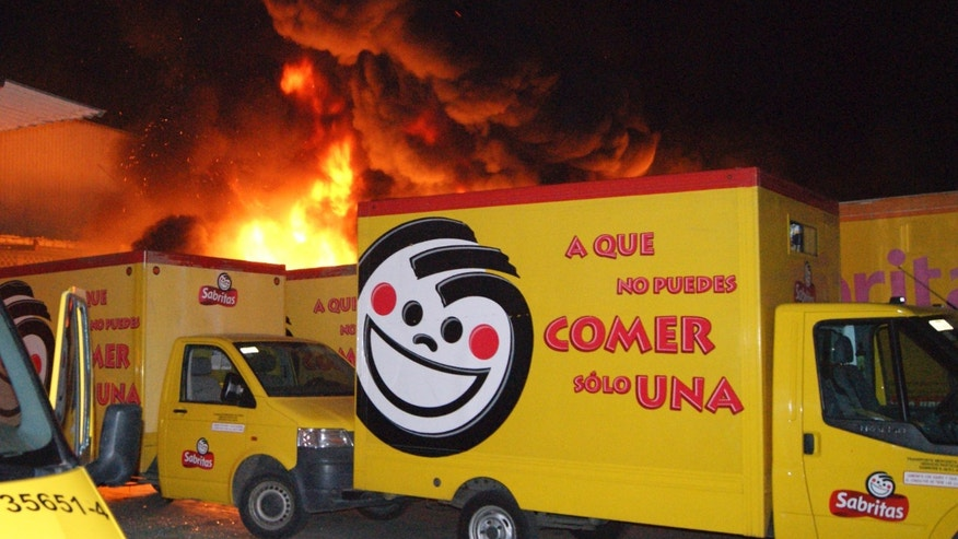 Friday, May 25, 2012. Flames rise from a warehouse of the Mexican potato-chip company Sabritas, in Lazaro Cardenas, Mexico. Sabritas is a subsidiary of PepsiCo. (AP Photo)