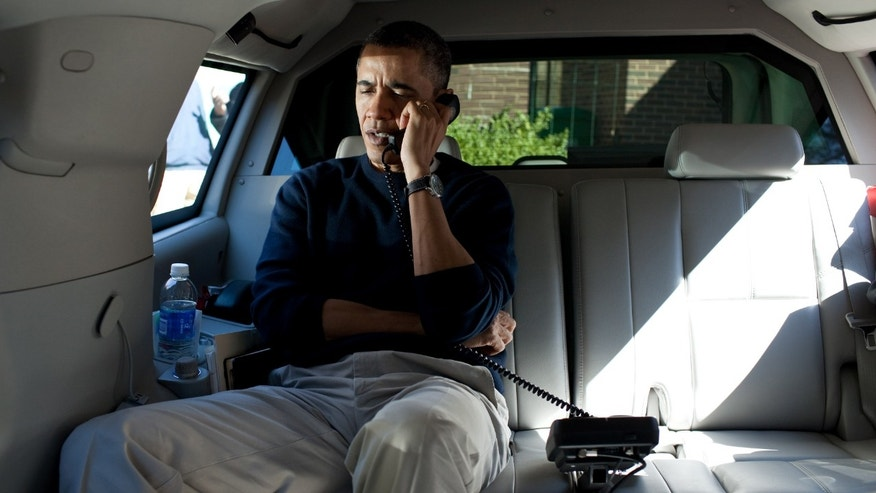 CHEVY CHASE, MD - MARCH 11:  In this handout from the White House, U.S. President Barack Obama talks on the phone with Afghanistan President Hamid Karzai from his vehicle outside the Jane E. Lawton Community Center March 11, 2012 in Chevy Chase, Maryland. According to reports March 15, 2012,  Afghan President Hamid Karzai wants Afghan forces to take over a year earlier in 2013 and wants U.S.  troops to pull out of villages after a U.S. soldier allegedly killed 16 Afghan civilians.  (Photo by Pete Souza/White House Photo via Getty Images)
