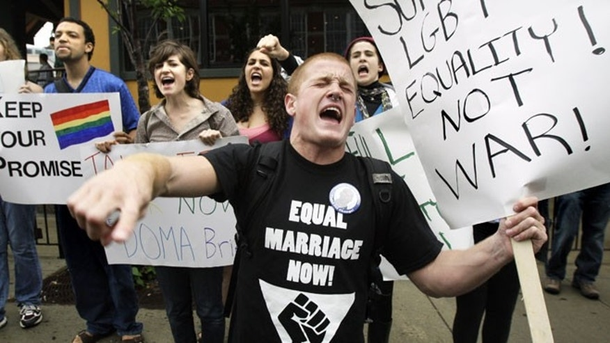 In this June 23, 2009 file photo, Keegan O'Brien of Worcester, Mass., leads chants as members of the LGBT community protest the Defense of Marriage Act outside a Democratic National Committee fundraiser in Boston.