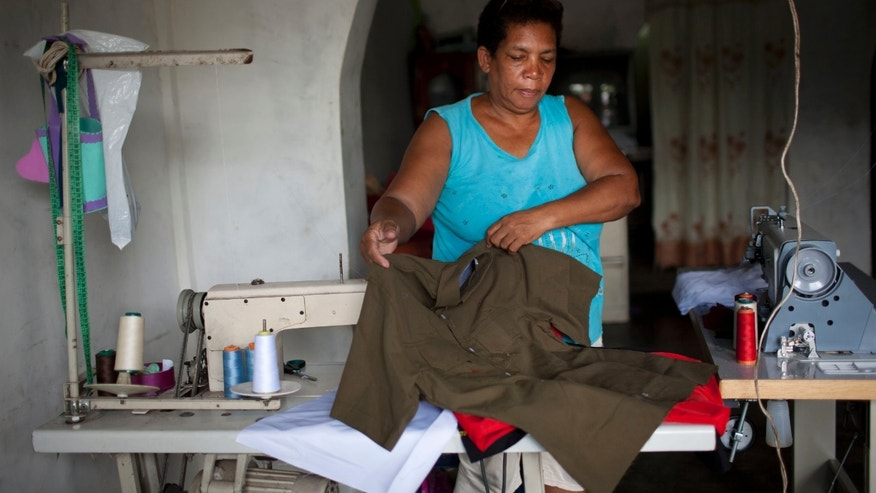 "In this May 31, 2012 photo, Petra Maria Rengifo displays a shirt she sewed as she works from her home in Legon, a neighborhood built along a highway in the countryside east of Caracas, Venezuela. One of the shirts made by the business that Rengifo supplies was picked up by an aide to opposition presidential hopeful Henrique Capriles. Now, Capriles wears almost nothing but Rengifo's short-sleeved, collared shirts on the campaign trail. In fact, the garments she sews have become so popular among the candidate's supporters that they're now called ""the Capriles shirt."" Venezuela will hold elections in October. (AP Photo/Ariana Cubillos)"