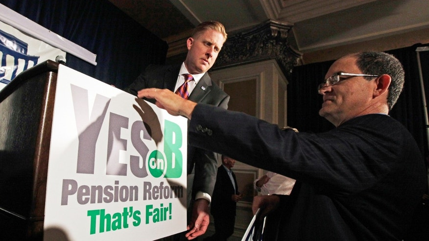 June 5, 2012:  Supporters of Proposition B, which would roll back public pensions, adjust a sign before a rally on election day in San Diego in this file photo.