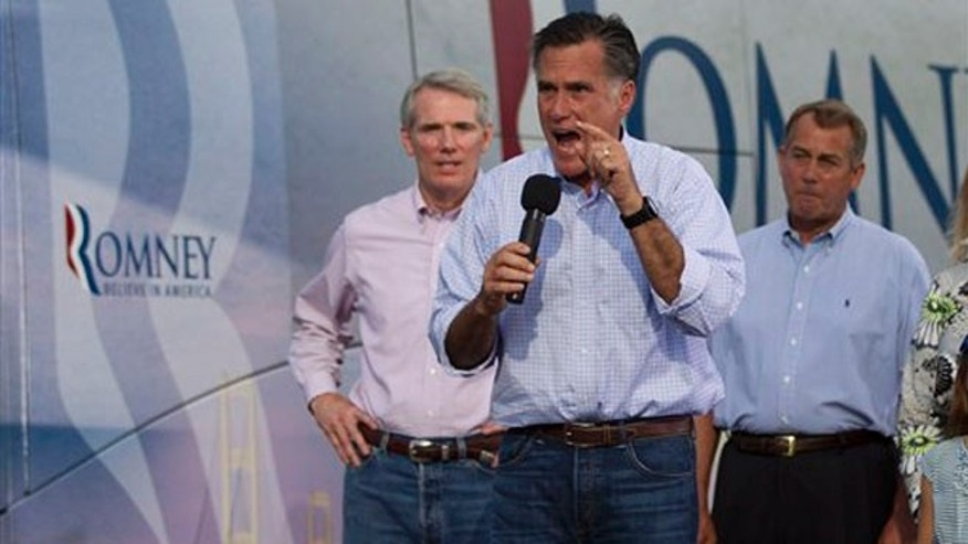 June 17, 2012: Mitt Romney gestures during a campaign stop in Troy, Ohio. From left, Sen. Rob Portman, R-Ohio, Romney, and House Speaker John Boehner.
