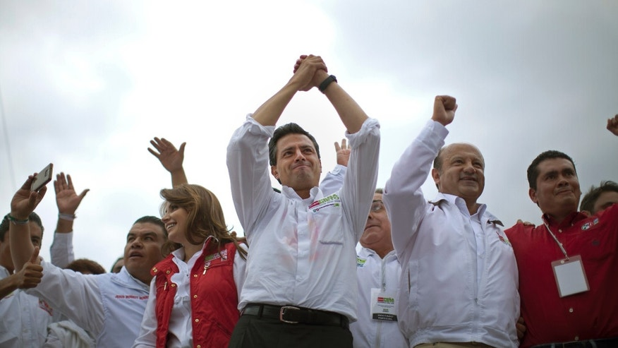 Presidential candidate Enrique Pena Nieto, of the Institutional Revolutionary Party, center, gestures to supporters during a campaign rally in Atlacomulco, Mexico, Sunday, June 17, 2012. Mexico will hold presidential elections on July 1. (AP Photo/Alexandre Meneghini)