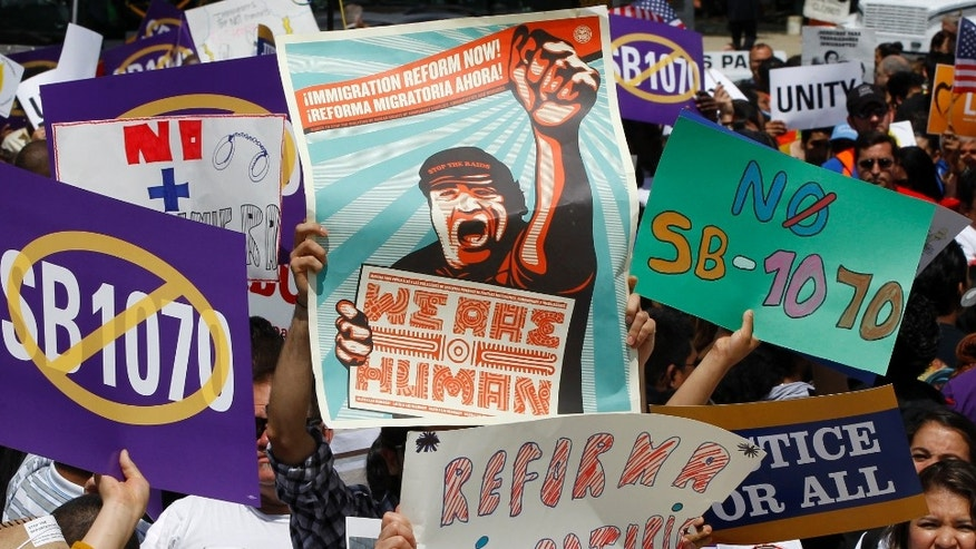 "Supporters of immigrant rights rally outside the Supreme Court in Washington, Wednesday, April 25, 2027, where the court held a hearing on Arizona's ""show me your papers"" immigration law. (AP Photo/Charles Dharapak)"