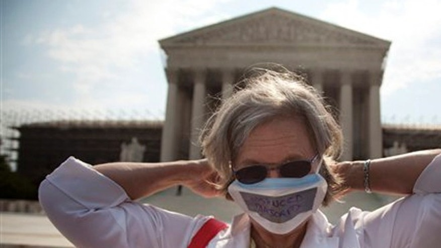 June 25, 2012: Carol Paris of Leonardtown, Md. demonstrates outside the Supreme Court in Washington.